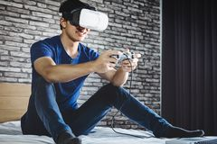 Young man have fun on bedroom in virtual reality headset or 3d g. Lasses playing video game, gaming and technology concept royalty free stock images