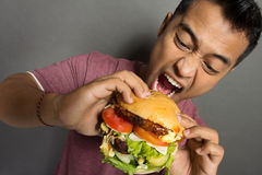 Young Man have a great desire to eat a burger Stock Images