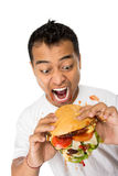 Young Man have a great desire to eat a burger. A portrait of young man have a great desire to eat a burger Royalty Free Stock Images