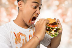 Young man have a great desire to eat a burger Royalty Free Stock Photos