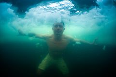 Young man haves recreational winter swim royalty free stock images