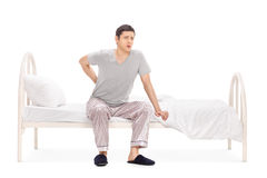 Young man having a back pain seated on a bed Stock Image