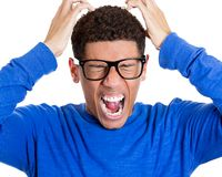 Young man having really bad headache, placing both hands on back of head Royalty Free Stock Images