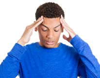Young man having really bad headache, placing both hands on temples Royalty Free Stock Photography