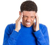 Young man having really bad headache placing both hands on temples Stock Photos