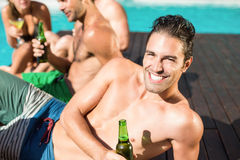 Young man having beer at the swimming pool. Young men having beer, friends interacting behind him at the swimming pool Royalty Free Stock Photography