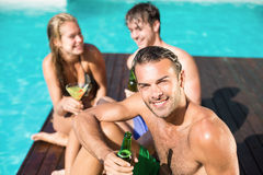 Young man having beer at the swimming pool Stock Image