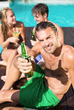 Young man having beer at the swimming pool Royalty Free Stock Image