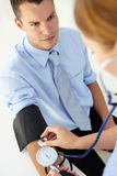 Young man having blood pressure taken Royalty Free Stock Photography