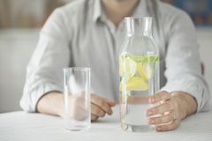 Young man having bottle of water and glass in kitchen stock images