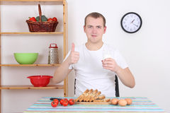 Young man having breakfast in the kitchen Stock Photos