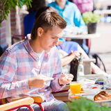 Young man having breakfast in outdoor cafe at european city Stock Photo