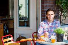 Young man having breakfast in outdoor cafe at european city drinking coffee Royalty Free Stock Photo