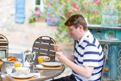 Young man having breakfast outside in summer Royalty Free Stock Photo