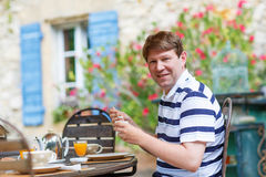 Young man having breakfast outside in summer Stock Photos