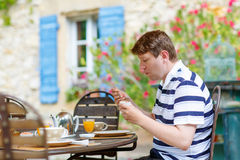 Young man having breakfast outside in summer with various jams, Stock Images