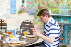 Young man having breakfast outside in summer with various jams, Royalty Free Stock Photos