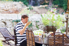Young man having breakfast outside in summer with various jams, Stock Photo