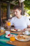 Young man having breakfast at resort restaurant Royalty Free Stock Photography