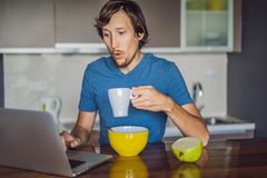 Young man having breakfast and using laptop on the kitchen stock photos