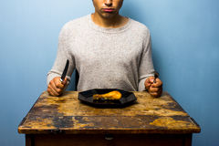 Young man having a chicken drumstick to eat Stock Photo