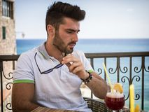 Young man having cocktail at outdoor bar stock images