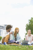 Young man having coffee while studying with female friends at college campus Stock Image
