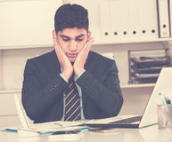 Young man is having complicated issue in project. In office Stock Image