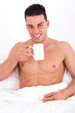 Young man having a cup of coffee in bed Royalty Free Stock Images