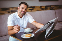 Young man having cup of coffee and eating pastry Royalty Free Stock Photography