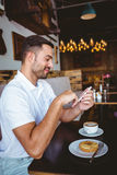 Young man having cup of coffee and pastry Royalty Free Stock Photos