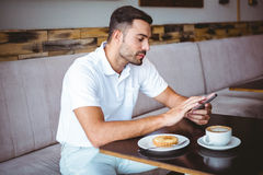 Young man having cup of coffee and pastry Royalty Free Stock Photo