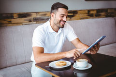 Young man having cup of coffee and pastry Stock Image