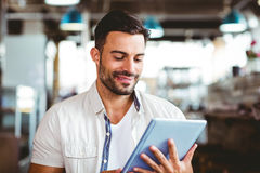 Young man having cup of coffee using tablet Stock Photography