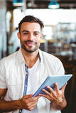 Young man having cup of coffee using tablet Royalty Free Stock Images