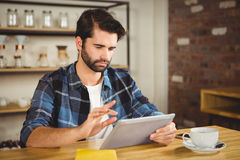 Young man having cup of coffee using tablet Royalty Free Stock Photo