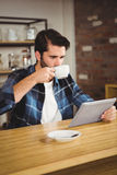 Young man having cup of coffee using tablet Stock Photo
