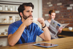 Young man having cup of coffee using tablet Royalty Free Stock Photos