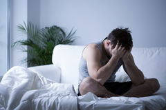 Young man having depression. Sitting on the bed Stock Image