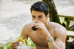 Young Man Having Fast Food Lunch at Picnic Table Royalty Free Stock Images