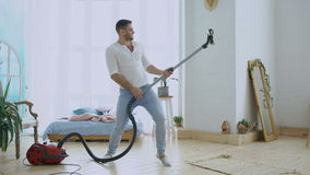 Young man having fun cleaning house with vacuum cleaner dancing like guitarist stock footage