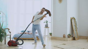 Young man having fun cleaning house with vacuum cleaner dancing like with woman stock footage
