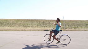 Young man having fun cycling. Handsome young man having fun cycling with hands in the air stock footage