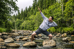 Young man is having fun hiking in Norway. Young man standing in mountain river among stones with raised up hands and screaming something Royalty Free Stock Photo