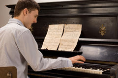 Young man having fun playing the piano Stock Image