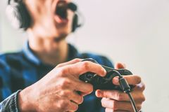 Young man having fun playing video games online using headphones and microphone - Close up male hands gamer holding a joystick royalty free stock photography