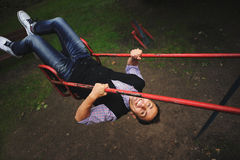 Young man having fun on swing on the playground. Young man in white shoes having fun on swing on the playground Royalty Free Stock Image