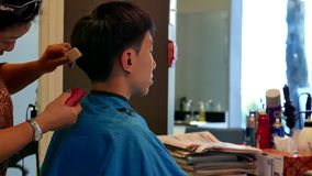 Young man having a hair cut in a hairdressing salon stock video footage