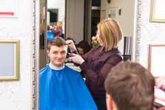 Young Man Having Hair Cut by Salon Stylist. Reflection in Mirror of Smiling Young Man Having Hair Cut and Styled by Blond Female Stylist in Salon royalty free stock photo
