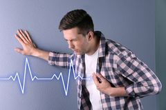 Young man having heart attack. On color background royalty free stock images